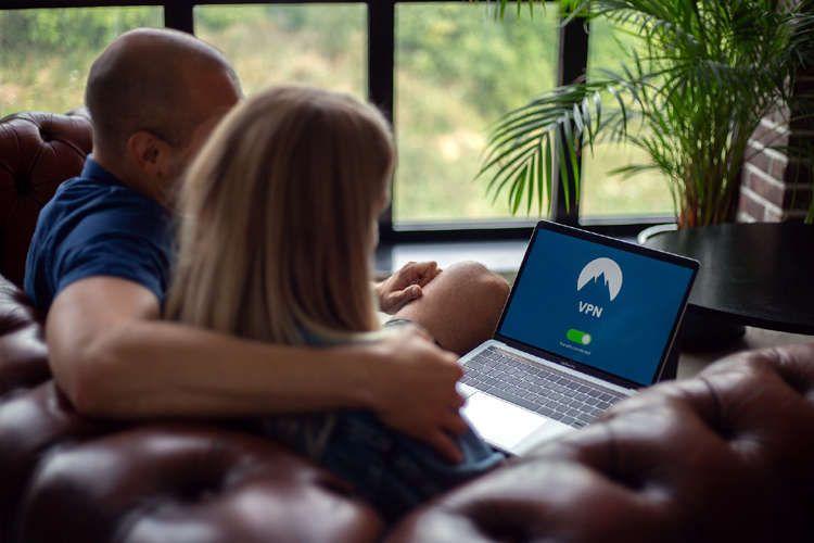 Pareja con un ordenador conectándose a una red VPN para ocultar su IP real