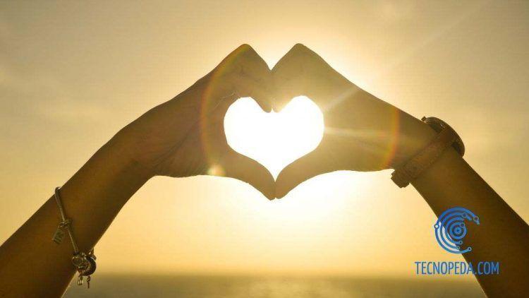 Manos haciendo un corazon en una puesta de sol