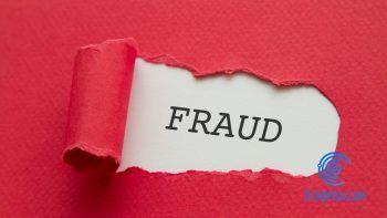 Papel rojo rasgado donde se lee fraude en inglés